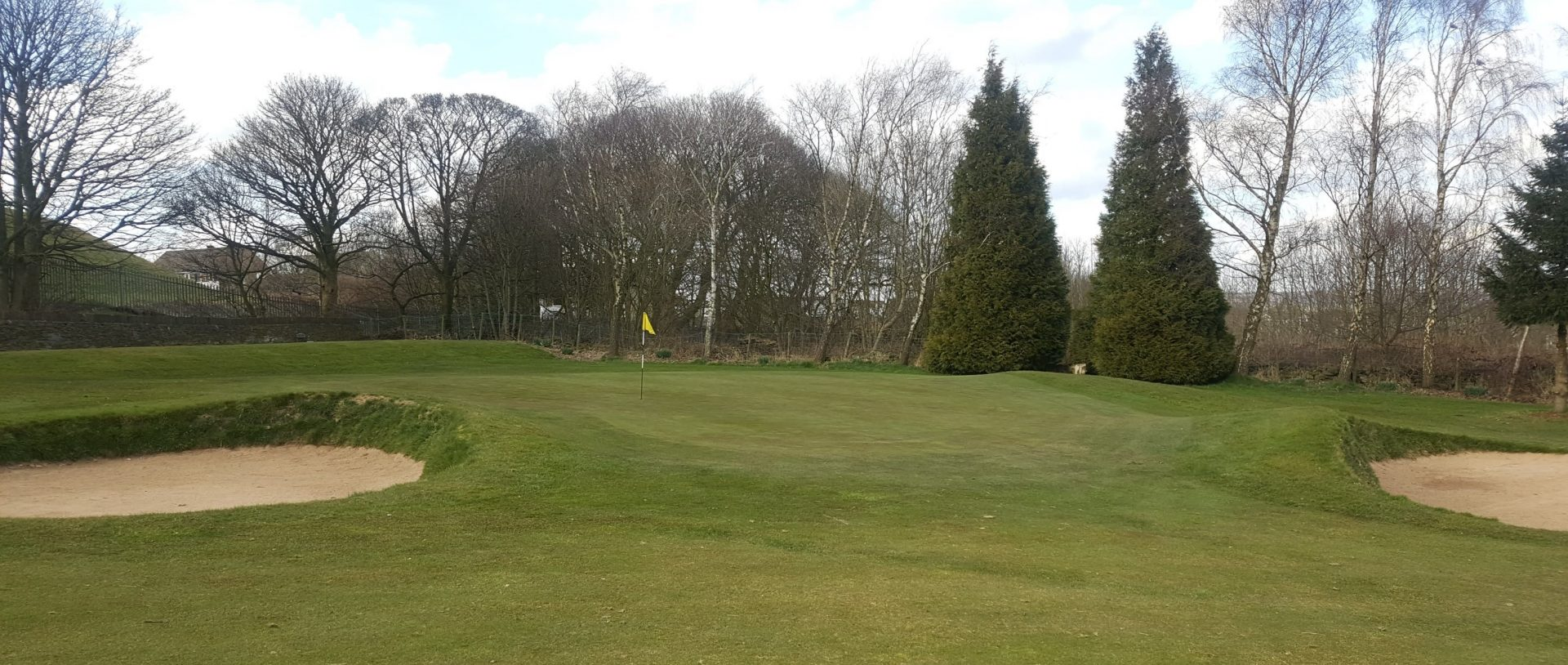 The contoured, sloping 1st Green.